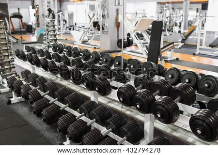 Rack with dumbbells at gym interior. Plenty of dumbbells on special rack at gym opposite the mirror. Mirror reflection of gym with dumbbells rack on foreground. - stock photo