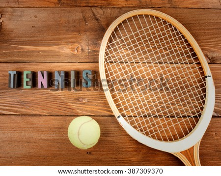racket and ball in wood background and word tennis in letterpress type