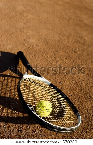 Racket and tennis ball on the tennis field, nice light, warm image - stock photo
