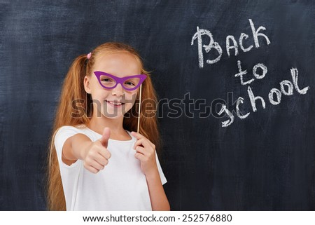 """Rad head pupil girl expressing positivity against the blackboard background with """"back to school"""" inscription, educational concept - stock photo"""
