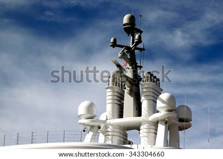 Radar system on to of a ship with blue cloudy sky in the background. - stock photo