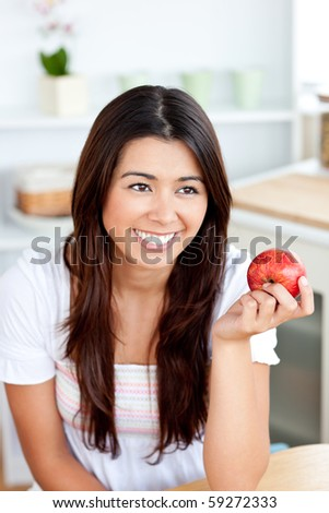 Radiant asian woman holding an apple in the kitchen at home - stock photo