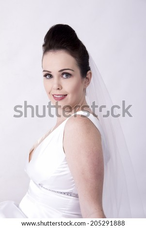 Radiant Bride wearing a while wedding gown smiling - stock photo