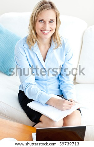 Radiant businesswoman writing in her notepad and using her laptop on a sofa at home