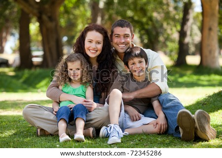 Radiant family sitting in the garden - stock photo
