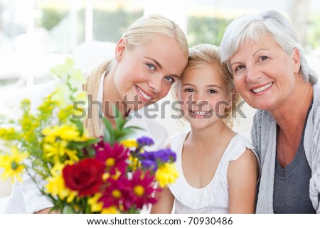 Radiant family with flowers at home - stock photo
