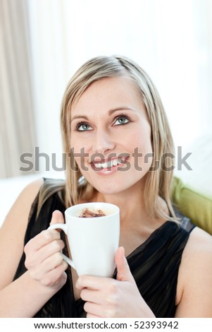 Radiant woman drinking a coffee sitting on a sofa at home