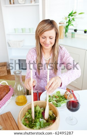 Radiant woman eating salad in the kitchen at home