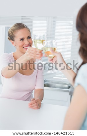 Radiant women having a toast with white wine in the kitchen