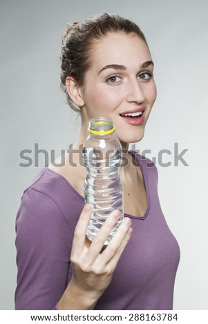 radiant young beautiful woman wearing purple shirt showing a bottle of citrus mineral water in foreground - stock photo