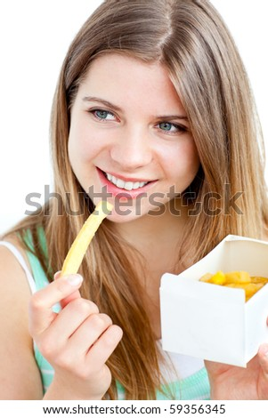 Radiant young woman eating fries against white background