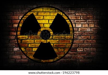 Radiation sign on a brick wall.  - stock photo