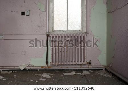 radiator and window in derelict hospital - stock photo