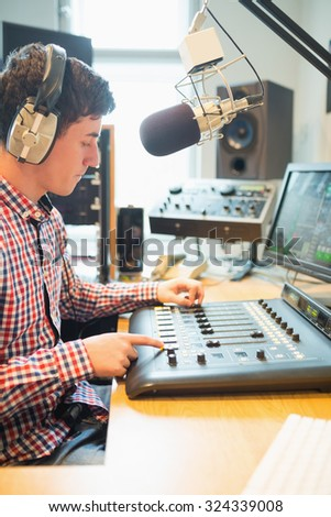 Radio host wearing headphones operating sound mixer on table in studio - stock photo