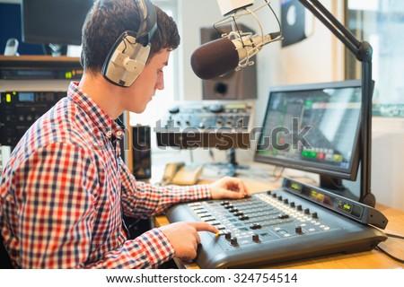 Radio host wearing headphones using sound mixer on table - stock photo