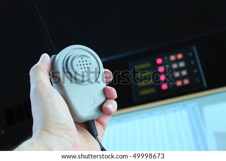 Radio microphone in man's hand against black background with illuminated LED switchboard - stock photo