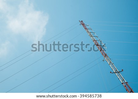 Radio or communication antenna tower against blue sky. - stock photo
