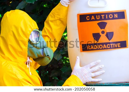 Radioactive waste ; Chemist in protective suit the disposal of radio active waste,photography - stock photo