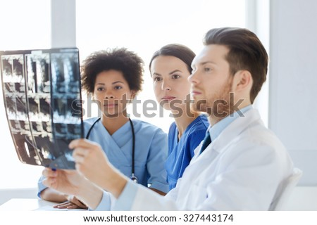 radiology, surgery, health care, people and medicine concept - group of doctors and nurses looking to and discussing x-ray image of spine at hospital - stock photo