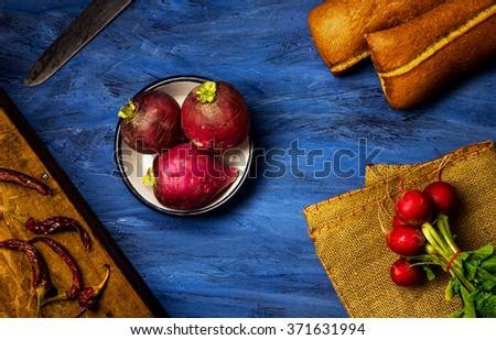 Radish , bread, pepper on blue background - stock photo