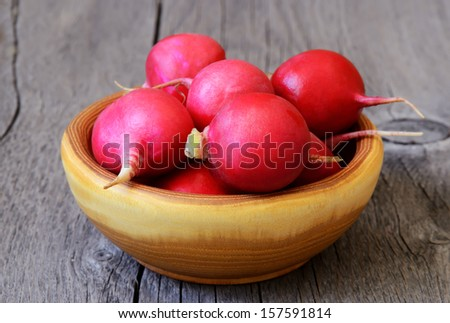 Radish in a brown bowl on wooden table - stock photo