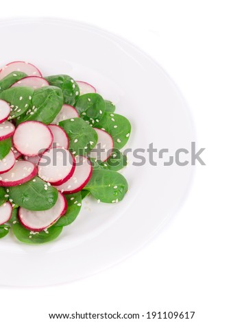 Radish salad with spinach and sesame. Isolated on a white background.