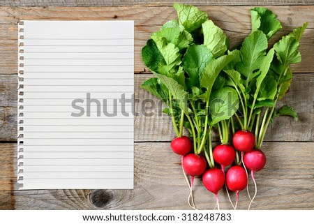 Radishes and paper for recipe on wooden background