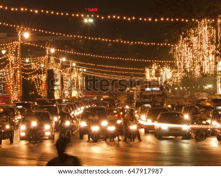 Radjadamnoen Avenue - a busy road in Bangkok, also known as the King's Road is lit up at night. Heavy traffic waits at the traffic lights. Resembles a Christmas scene.