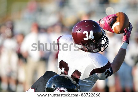 RADNOR, PA - NOVEMBER 12: A Lower Merion receiver (#15) makes a leaping catch  during the 115th meeting of Radnor and Lower Merion High School football teams November 12, 2011 in Radnor, PA - stock photo
