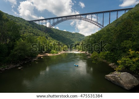 Rafters float towards the rapids under the high arched New River Gorge bridge in West Virginia