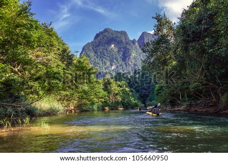 Rafting on a canoe on tropical river in a national park Khao Sok - stock photo