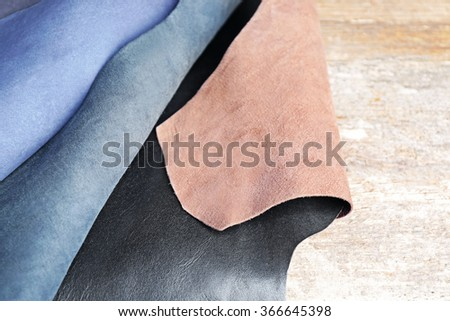 Ragged leather material wrong side, on the wooden table, close-up - stock photo