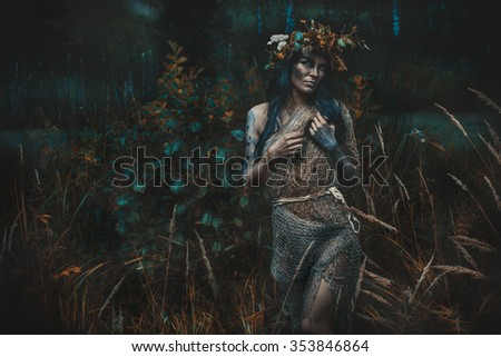 Ragged woman staying in the yellow grass near the river