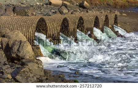 Raging Floodwater Drains Through Six Large Industrial Culvert Pipes - stock photo