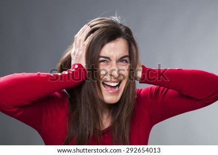 raging young woman having painful headache, covering closed ears, annoyed by noisy music, ignoring someone, not wanting to hear their side of story