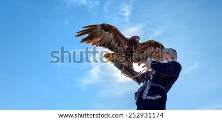 "RAHAT, KAZAKHSTAN - FEBRUARY 14: Eagle on man's hand in Rahat near Almaty on February 14, 2015 in Rahat, Kazakhstan. Annual national competition with birds of prey ""Sonar - 2015"" - stock photo"