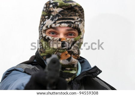 raider in ski mask, pointing a handgun