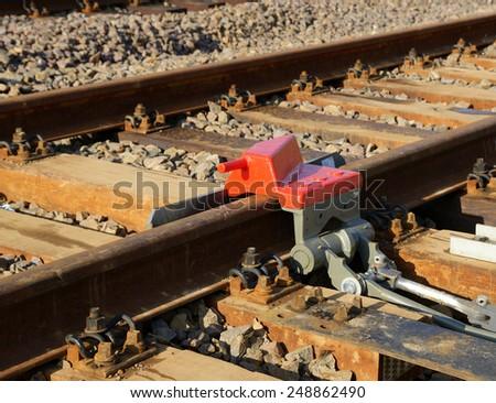 Rail brakes on the tracks siding on sunny day - stock photo