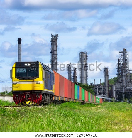 Rail freight, containers, against a backdrop of an oil refinery. - stock photo