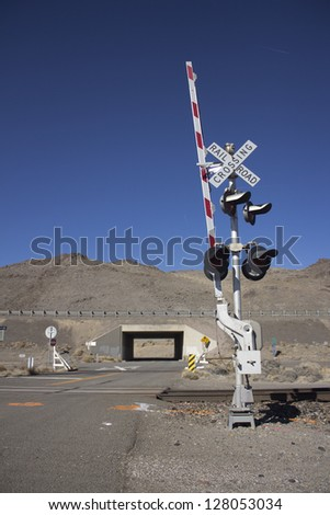 rail road crossing signal with blue skies in the desert. - stock photo