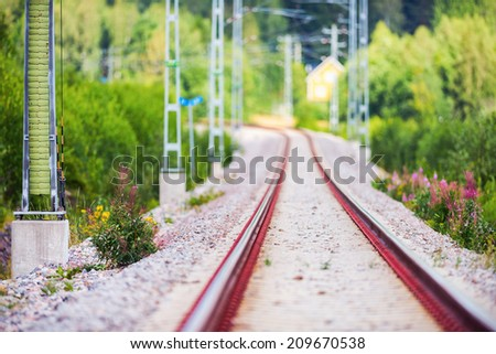 Rail track in a curvy section with short depth of field in beautiful landscape, Sweden - stock photo