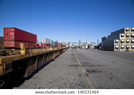 Rail yard with containers loaded onto train with flat deck trucks - stock photo