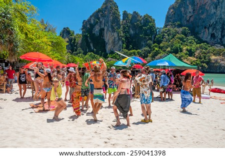 RAILAY, THAILAND - MARCH 13, 2014: Dancing Toutrists while making movie at West Railay beach, one of the most popular rock climbing locations in Asia. on March 13, 2014. Railay, Krabi, Thailand - stock photo