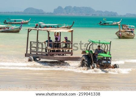 RAILAY, THAILAND - MARCH 13, 2014: Toutrists transport from mainland by boats to East Railay beach, one of the most popular rock climbing locations in Asia. on March 13, 2014. Railay, Krabi, Thailand  - stock photo