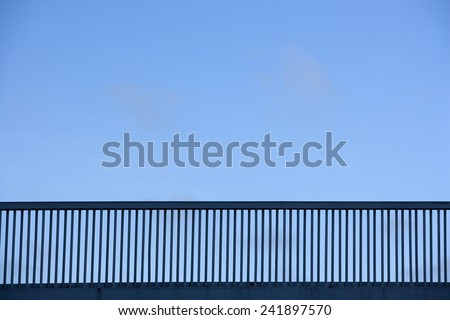 Railing of bridge towards blue sky - stock photo
