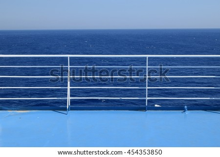 Railings on ferry boat cruise ship deck. Blue sea and sky summer travel background. - stock photo