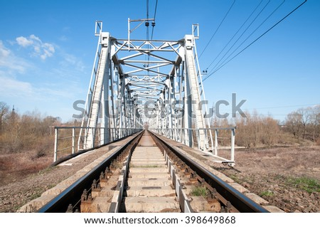 railroad bridge of steel, inside view passes over the river, around the trees - stock photo