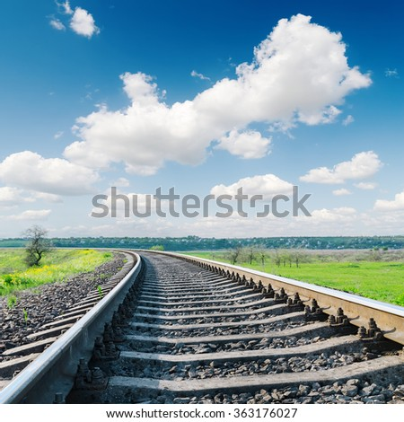 railroad closeup to horizon and white clouds in blue sky