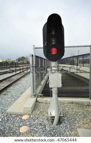 Railroad colored light signal (replacing old semaphor signals) shows red stop for oncoming trains - stock photo