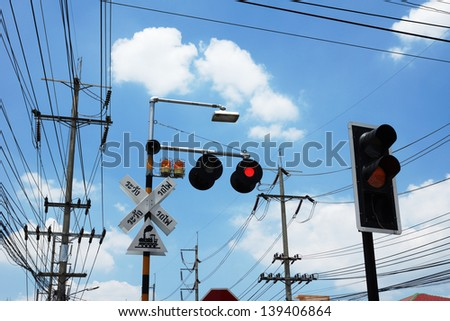 railroad crossing gate sign with electric poles under the blue sky - stock photo